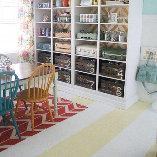 This craft room has cement floors that needed a whimsical touch to match the rest of the space. Bold yellow and white stripes are exactly what this kind of creative area called for