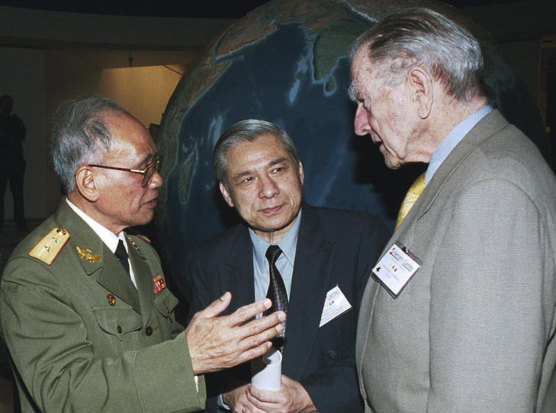 FILE - In this April 1999 file photo, retired Adm. Elmo R. Zumwalt Jr., right, talks with old foes, Vietnamese Lt. Gen. Nguyen Dinh Uoc, left, and Senior Col. Vo Dinh Quang, center, at a symposium hosted by the Vietnam Center of Texas Tech University at Lubbock, Texas. A Navy destroyer bearing Zumwalt's name will be christened by his two daughters during a ceremony Saturday, April 12, 2014 at Bath, Maine. (AP Photo/Neal Ulevich, File)