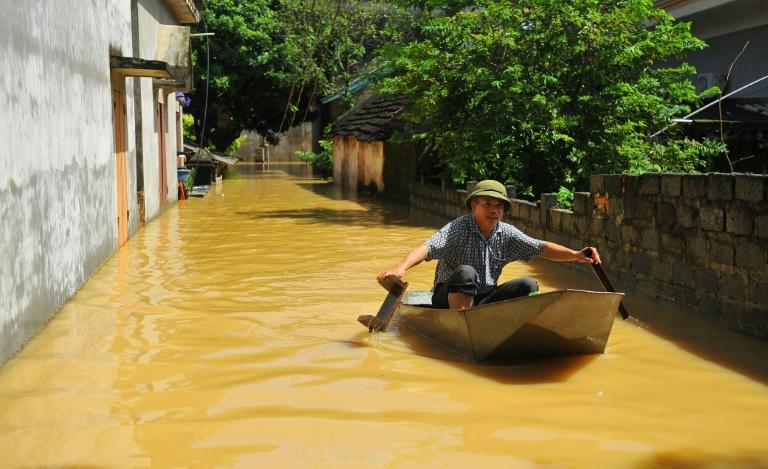 A Vietnamese villager crosses a flooded alley using a boat in the northern province of Ninh Binh, on October 12, 2017