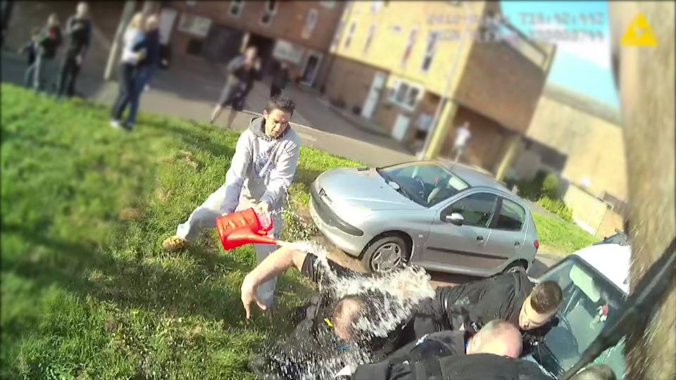 This image shows the moment eight police officers had petrol thrown over them, with two of the officers hospitalised after digesting the liquid. (PA)