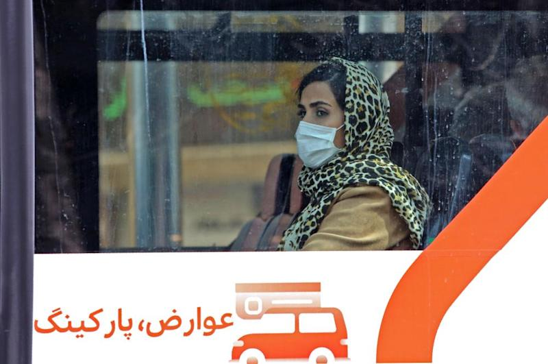 A bus passenger wears a protective mask in Tehran