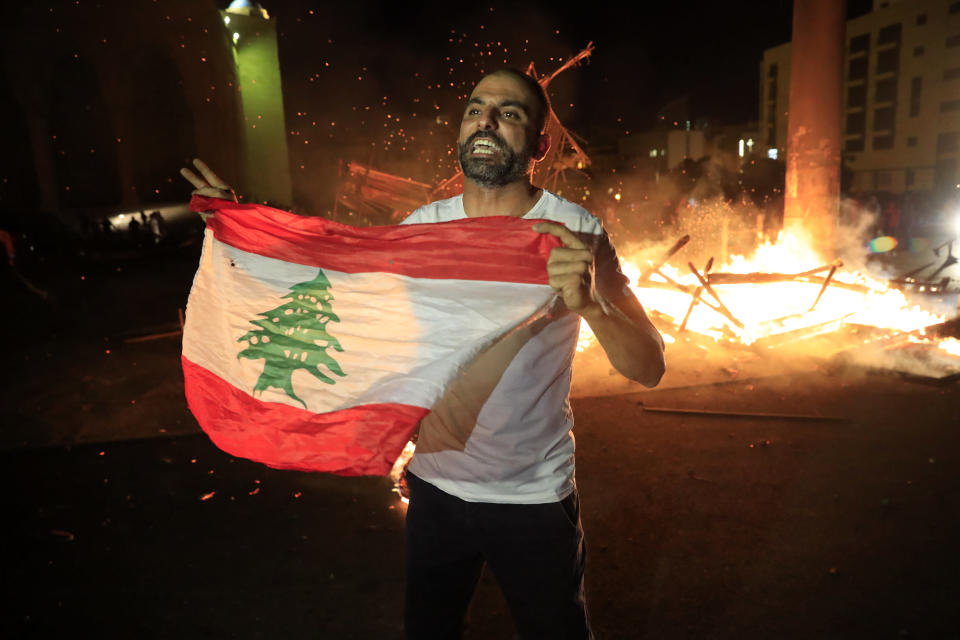 A protester holds the Lebanese flag and shouts slogans denouncing the naming of former Lebanese Prime Minister Saad Hariri as a potential candidate for prime minister, after Hariri's supporters burned a significant protest symbol erected in downtown Beirut, Lebanon, Wednesday, Oct. 21, 2020. Hariri resigned a year ago amid nationwide protests against government corruption and mismanagement of Lebanon's resources. (AP Photo/Hussein Malla)