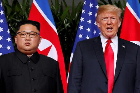 FILE PHOTO: U.S. President Donald Trump and North Korean leader Kim Jong Un react at the Capella Hotel on Sentosa island in Singapore