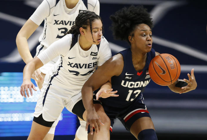Connecticut guard Christyn Williams, right, takes control of a loose ball in front of Xavier guard Shaulana Wagner (24) during the first half of an NCAA college basketball game Saturday, Feb. 20, 2021, in Cincinnati. (AP Photo/Gary Landers)