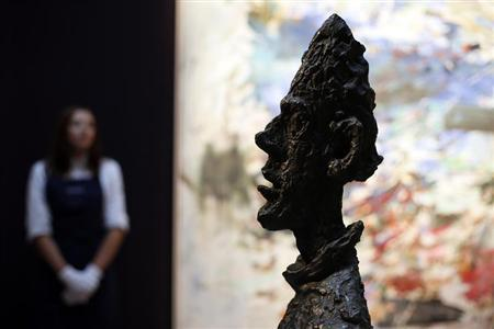 "A Sotheby's employee stands behind Giacometti's artwork ""Grande tete de Diego"" at Sotheby's auction house in London"