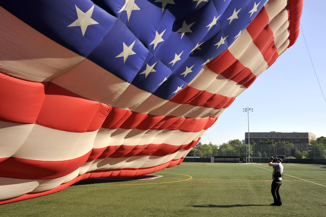 A photographer takes a picture of the PNC American Flag balloon as it's inflated in honor of America for Independence Day on the De Baun Athletic Complex at Stevens Institute of Technology on July 3, 2012 in Hoboken, New Jersey. The 53 by 78 foot balloon is the world's largest free-flying American flag, weighs 530 pounds and is being flown in the upcoming 30th annual NJ Festival of Ballooning. (Photo by Michael Bocchieri/Getty Images)