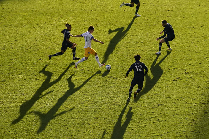 San Jose Earthquakes midfielder Carlos Fierro (21) moves the ball under pressure from a group of Sporting Kansas City players during the first half of an MLS soccer match Sunday, Nov. 22, 2020, in Kansas City, Kan. (AP Photo/Charlie Riedel)