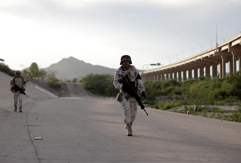 Members of the Mexican National Guard patrol along the banks of the Rio Bravo river at the border between Mexico and U.S. as seen from Ciudad Juarez, Mexico July 19, 2019. REUTERS/Daniel Becerril