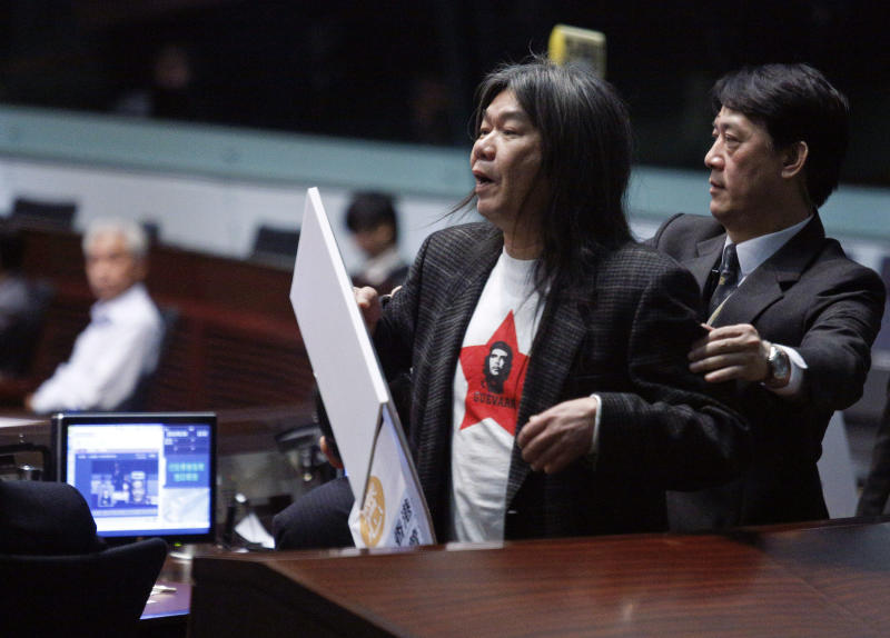 Hong Kong Legislative Council member Leung Kwok-hung, left, also known as Long Hair, is taken away by security guards while the Hong Kong Chief Executive Leung Chun-ying is delivering his policy address at the Legislative Council in Hong Kong Wednesday, Jan. 16, 2013. Leung focused on the social problems such as housing, pollution and economic development for the next five years. (AP Photo/Vincent Yu)