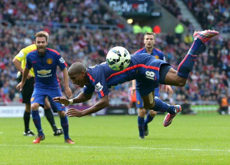 Manchester United's midfielder Ashley Young falls to the ground after a challenge by Sunderland's defender Wes Brown on August 24, 2014