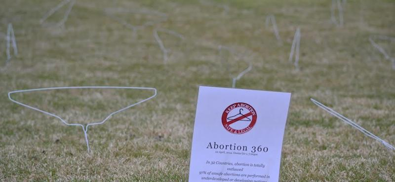 glorify abortion with WIRE COAT HANGER display on college lawn