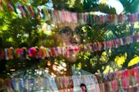 Cathy Tobias, 67, poses as she looks out at her colorful Covid memorial -- she and her friend devised a system to keep track of the dead