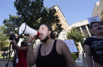 Raynie Castaneda leads a chant against Texas Gov. Greg Abbott across the street from the building where he signed Senate Bill 1, also known as the election integrity bill, into law in Tyler, Texas, Tuesday, Sept. 7, 2021. The sweeping bill signed by the two-term Republican governor further tightens Texas' strict voting laws. (AP Photo/LM Otero)