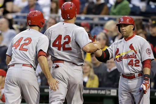St. Louis Cardinals' Carlos Beltran, right, greets Matt Holliday, center, and Matt Carpenter, after they scored on a double by Cardinals' Allen Craig Pittsburgh Pirates starting pitcher James McDonald during the second inning of a baseball game in Pittsburgh Monday, April 15, 2013. Players on both teams wore No. 42 in honor of Jackie Robinson. (AP Photo/Gene J. Puskar)