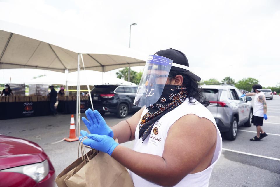 Austin, Texas made Tito's Handmade Vodka visits Brownsville, Texas Sports Park Satruday, Aug. 1, 2020, to distribute thousands of Tito's made hand cleanser sanitizer to thousands of Brownsville residents to help fight the spread of COVID-19. (Miguel Roberts/The Brownsville Herald via AP)/The Brownsville Herald via AP)
