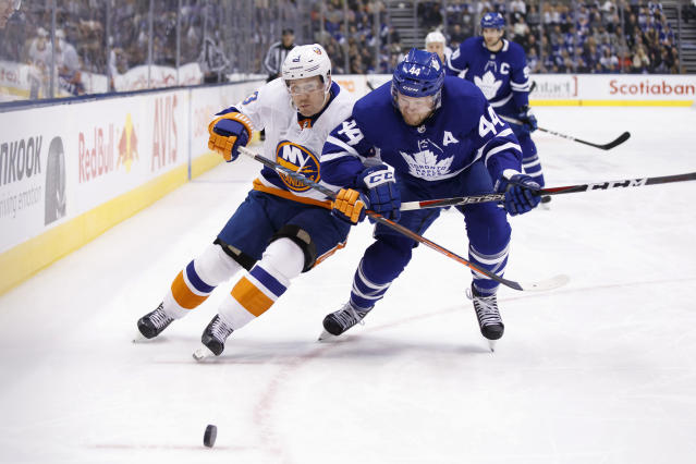 Toronto Maple Leafs defenceman Morgan Rielly (44) and New York Islanders center Casey Cizikas (53) vie for the puck during first period of an NHL hockey game in Toronto, Saturday, Jan. 4, 2020. (Cole Burston/The Canadian Press via AP)