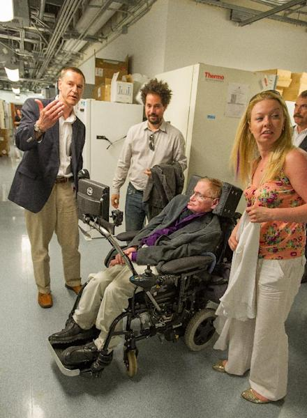 In this photo provided by Cedars-Sinai, Clive Svendsen, PhD, left, director of the Cedars-Sinai Regenerative Medicine Institute, leads Stephen Hawking, third from left, on a tour of the Regenerative Medicine Institute at Cedars-Sinai Medical Center in Los Angeles on Tuesday, April 9, 2013. Others are unidentified. (AP Photo/Cedars-Sinai, Eric Reed)