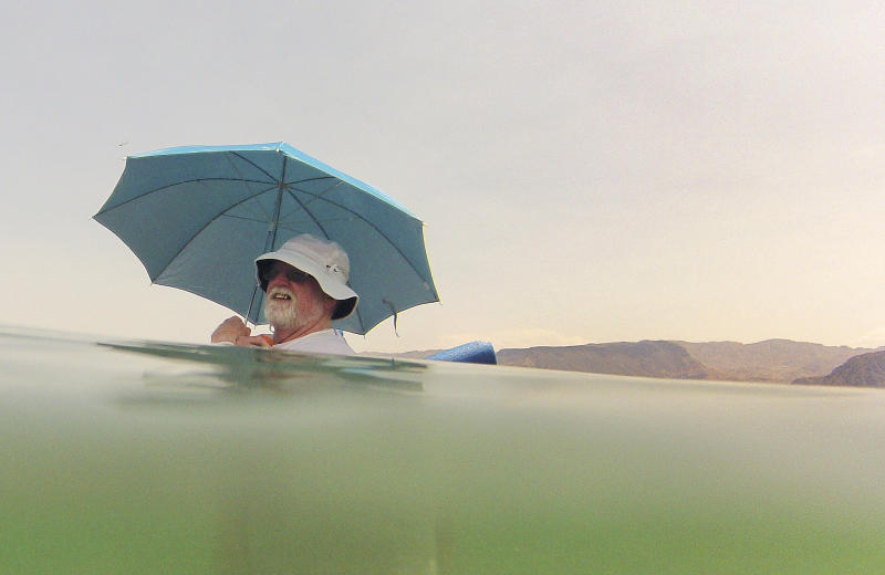 Mike Bouse of Henderson, Nev., shades himself with an umbrella as he floats in the waters along Boulder Beach at Lake Mead, Saturday, June 29, 2013 near Boulder City, Nev. Bouse and his wife planned to spend most of the day in and out of the water to escape the heat in the Las Vegas area where Saturday's daytime high was expected to reach 117 degrees, the city's all-time high. It was 108 at noon Saturday in Sin City. (AP Photo/Julie Jacobson)