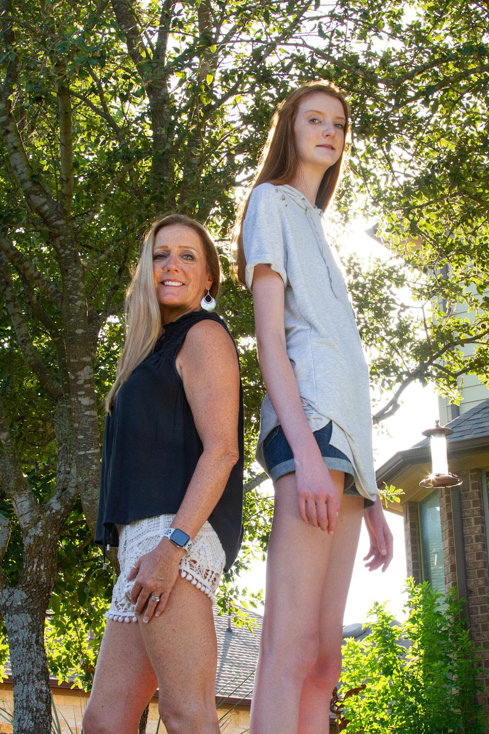 ***EXCLUSIVE VIDEO AVAILABLE*** AUSTIN, TX, USA - 11 AUGUST 2019: 16-year-old Maci Currin, whose 53 inch long legs are believed to be the world's longest, towers over her mother Trish as the pair stand back-to-back on 11 August, 2019, in Austin, Texas.A TOWERING teenager from Texas is about to strut her way into the record books as the proud owner of the world's longest legs. Aged only 16, Maci Currin, from Austin, Texas, has legs measuring an incredible 53 inches - smashing the previous record of 52.2 inches held by Ekaterina Lisina, of Russia. The 6ft 9in aspiring model was only 19 inches when born, but a series of growth spurts meant she rocketed to 5ft 7in by the time she was nine years old. Maci also has an inseam of 43 inches and has to stoop to avoid banging her head when walking through doors, but says she is proud of her lengthy limbs despite the added attention they bring. PHOTOGRAPH BY: Bradley Beesley / Barcroft Media (Photo credit should read Bradley Beesley / Barcroft Media / Barcroft Media via Getty Images)