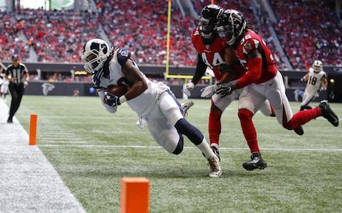 Todd Gurley #30 of the Los Angeles Rams makes the reception for a touchdown as Vic Beasley #44 and Jamal Carter #35 of the Atlanta Falcons defend in the first half of an NFL game at Mercedes-Benz Stadium on October 20, 2019 in Atlanta, Georgia - Credit: Getty Images