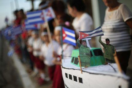 A miniature replica of the Granma yacht carries figures of Fidel and Raul Castro, as people await the arrival of the caravan carrying the ashes of Fidel Castro in Guaimaro, Cuba, December 2, 2016.  REUTERS/Edgard Garrido/Files
