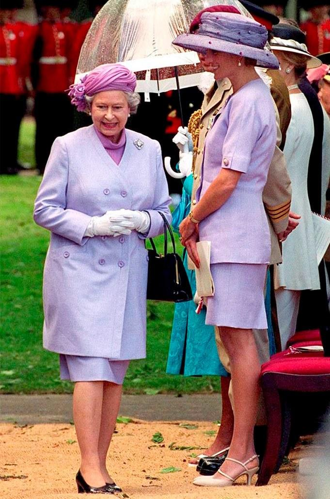 Queen Elizabeth II with Princess Diana in matching looks at the unveiling of the Canada memorial monument in Green Park. She and Prince Charles would announce plans to divorce the following year.