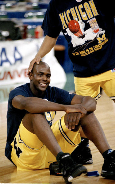 FILE - Michigan's Chris Webber gets a pat on the head after being named MVP of the NCAA West regional final in Seattle, Wa., in this March 29, 1993 file photo. Michigan's 10-year, NCAA-issued dissociation from Webber, Taylor, Bullock ends. On Wednesday, May 8, 2013 the school and the former basketball players can renew their relationship if they choose. (AP Photo/Susan Ragan, File)
