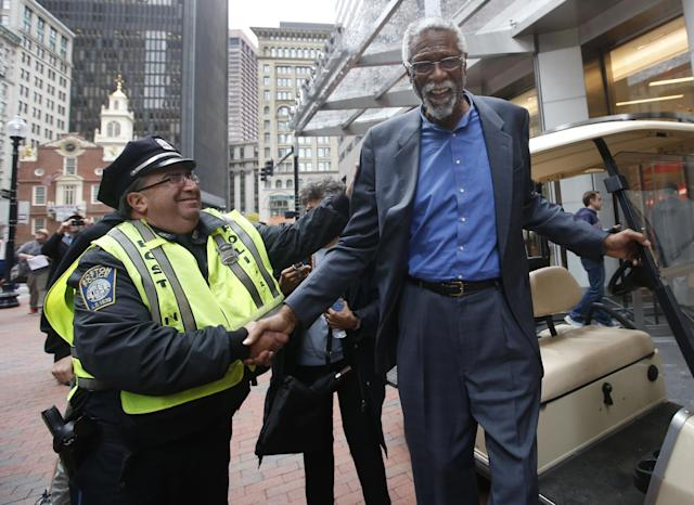 Boston Police officer Jim Cody shakes hands with former Boston Celtics basketball star Bill Russell after a statue honoring him was unveiled at City Hall Plaza in Boston, Friday, Nov. 1, 2013. (AP Photo/Elise Amendola)