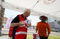 Salvation Army hydration station volunteer Paul Spiri, left, hands out water during a heatwave as temperatures hit 115-degrees Tuesday, June 15, 2021, in Phoenix. (AP Photo/Ross D. Franklin)