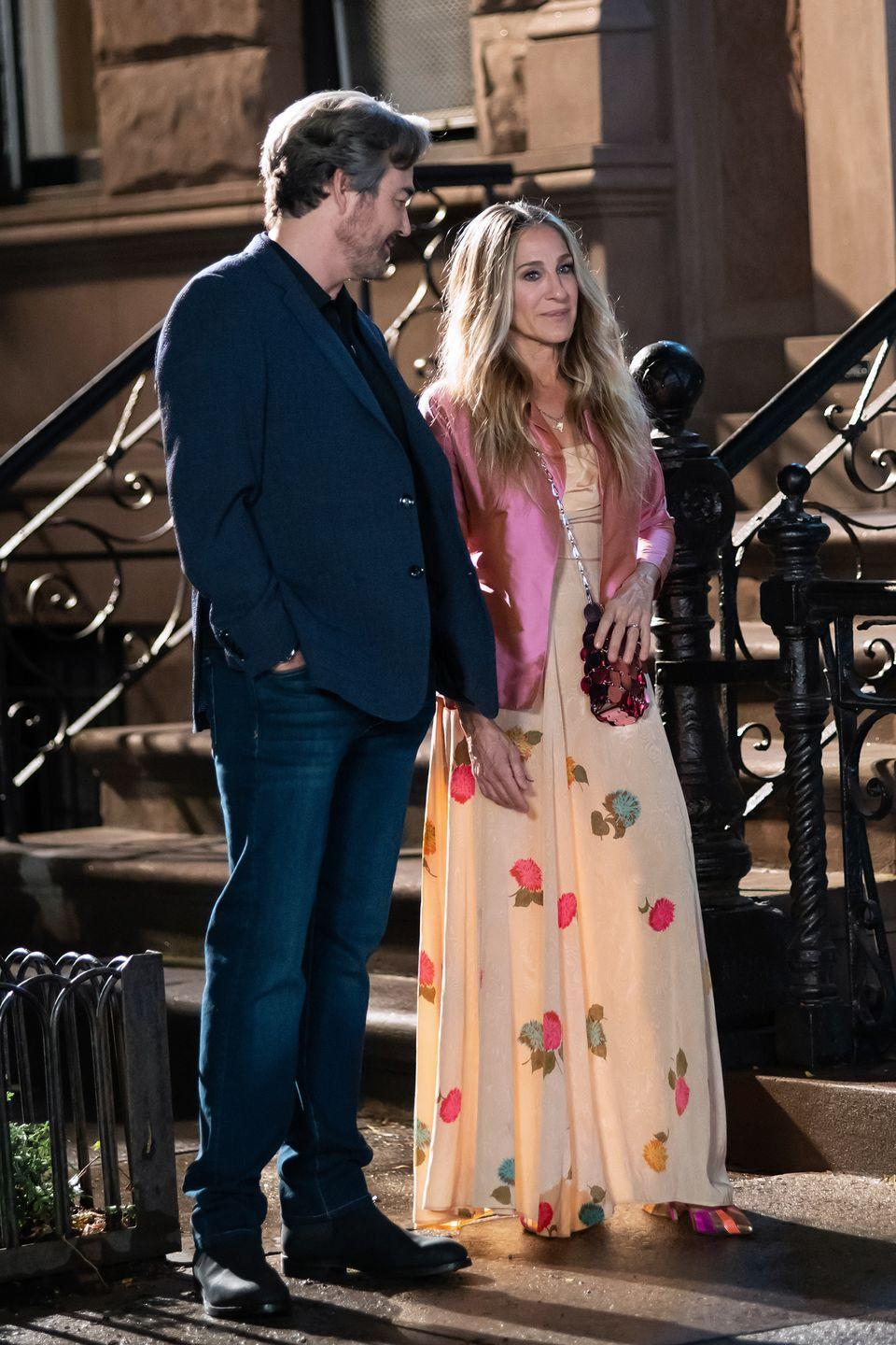 <p>In character as Carrie, the star wore a cream-coloured dress decorated with embroidered flowers in different colours, styled with a pink satin blazer and sequinned pink bag. </p><p>SJP's team accessorised the evening ensemble with multicoloured pointed-toe heels.</p>