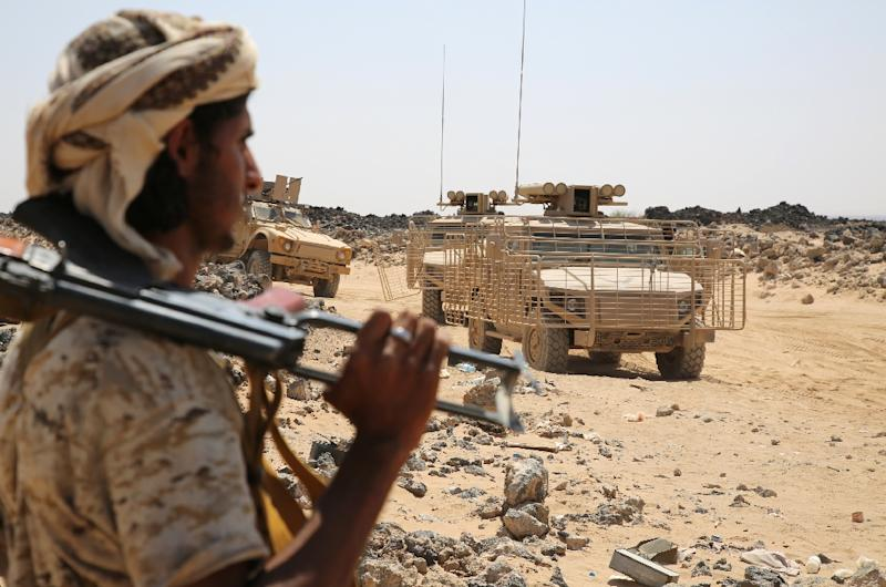 An armed Yemeni man from the Popular Resistance Committees, supporting forces loyal to fugitive President Abedrabbo Mansour Hadi, stands next to an armoured vehicle in Marib province on September 14, 2015 (AFP Photo/Abdullah Hassan)