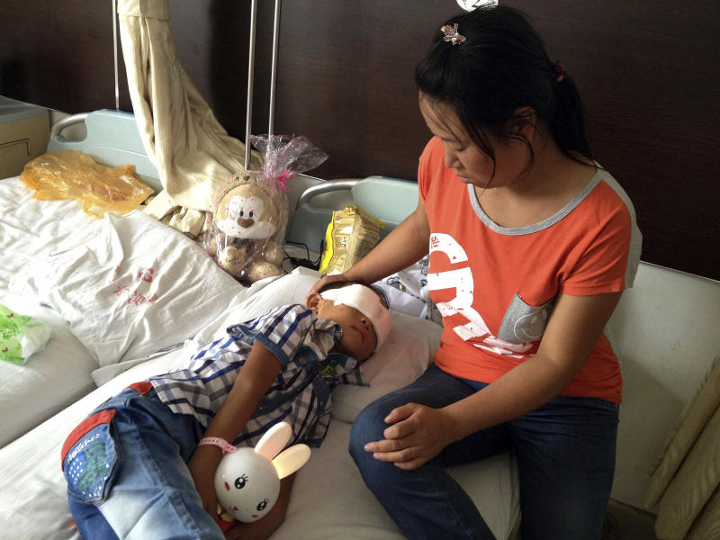 Guo Bin recuperates near his mother from an attack in the rural area of Linfen city that left him blind in a hospital in Taiyuan in northwest China's Shanxi province on Wednesday, Aug. 28, 2013. A woman tricked the 6-year-old boy into going into a field, and then gouged out his eyes, police said Wednesday. (AP Photo) CHINA OUT
