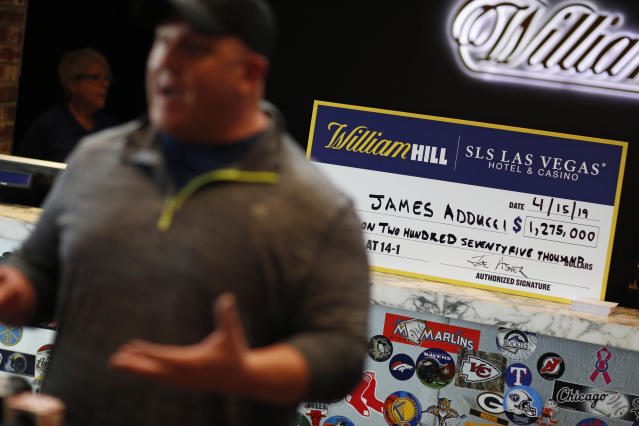 James Adducci speaks with the media in front of a novelty check after winning more than one million dollars betting on Tiger Woods winning the Masters, Monday, April 15, 2019, in Las Vegas. (AP Photo/John Locher)