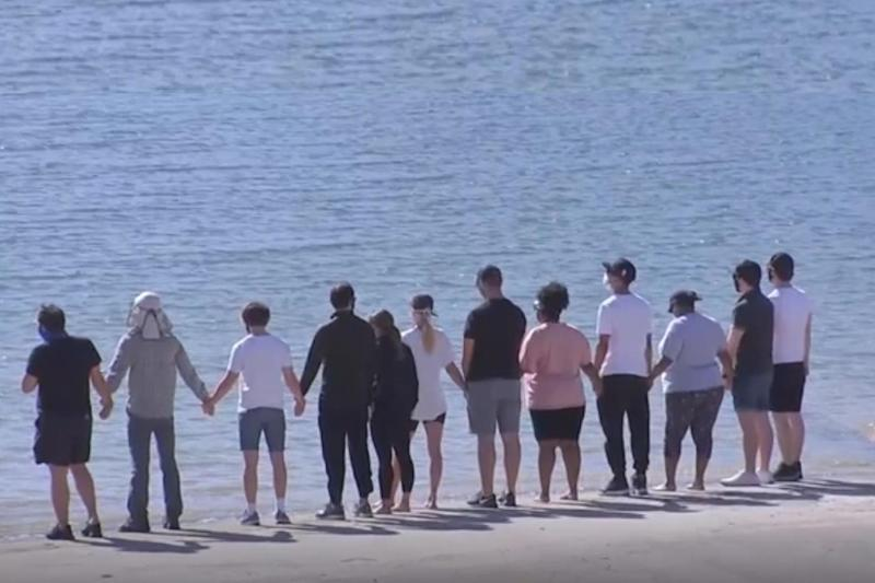 In mourning: The Glee cast joined hands by the lake where Rivera's body was recovered (ABC)