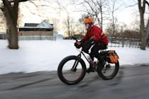 In a Feb. 19, 2014, photo, Fraser Cunningham, 56, of Madeira, Ohio, a General Electric engineer, bicycles home from work in single-digit temperatures. Cunningham hasn't missed a day biking to and from work for a year and a half. (AP Photo/The Cincinnati Enquirer, Carrie Cochran) MANDATORY CREDIT; NO SALES