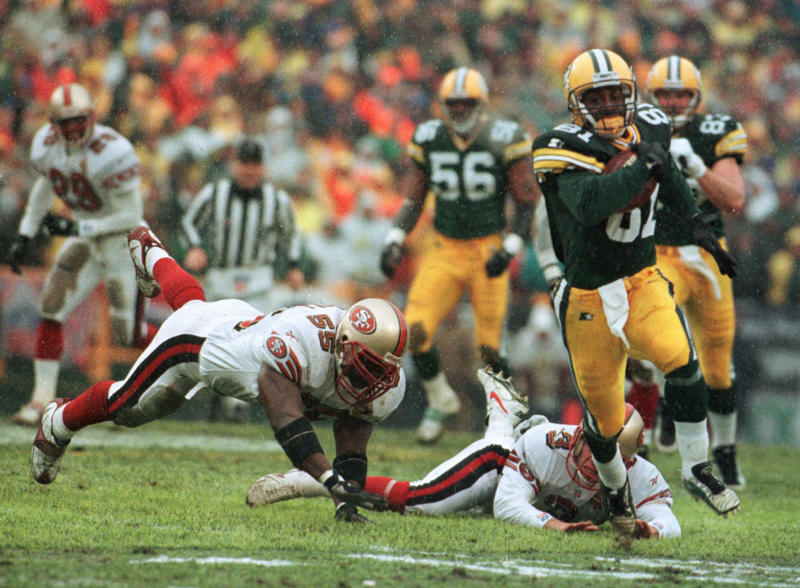 FILE - In this Jan. 4, 1997, file photo, Green Bay Packers' Desmond Howard eludes San Francisco 49ers Kevin Mitchell (55) and punter Tommy Thompson on the way to a touchdown on a punt return in the first half of an NL football game in Green Bay, Wisc. The two teams that have combined for nine Super Bowl titles will meet with a spot in the ultimate game on the line once again when the 49ers (14-3) host the Packers (14-3) in the NFC championship game on Sunday, Jan. 19, 2020.(AP Photo/David Boe, File)