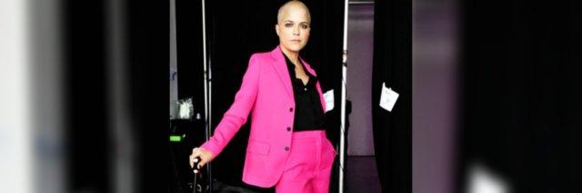 Selma Blair wearing a sexy pink and black suit. Her head is shaved.