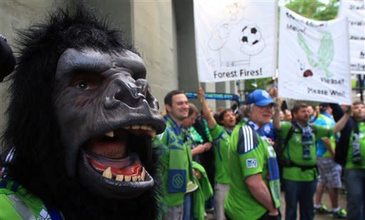 Seattle Sounders fans celebrate before the start of an MLS soccer game between the Sounders and the Portland Timbers, Sunday, June 24, 2012, in Portland, Ore. (AP Photo/Rick Bowmer)