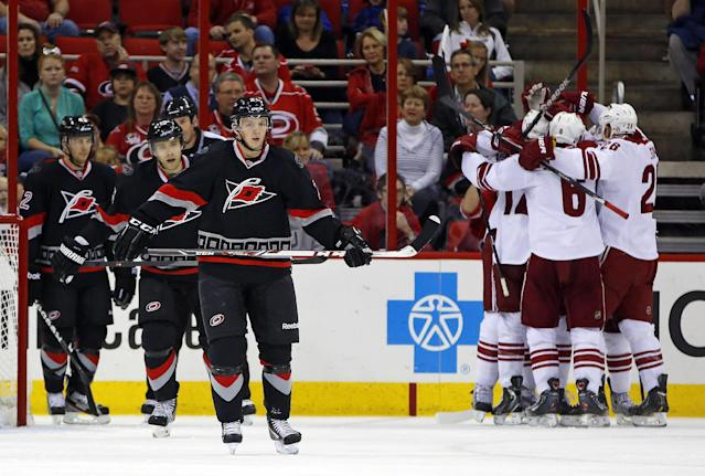 The Phoenix Coyotes celebrates a goal by Rob Klinkhammer as Carolina Hurricanes' Brett Sutter (42), far left, Drayson Bowman (21), second from left and Tuomo Ruutu (15) of Finland, skate away during the second period of an NHL hockey game, Sunday, Oct. 13, 2013, in Raleigh, N.C. Phoenix defeated Carolina 5-3. (AP Photo/Karl B DeBlaker)