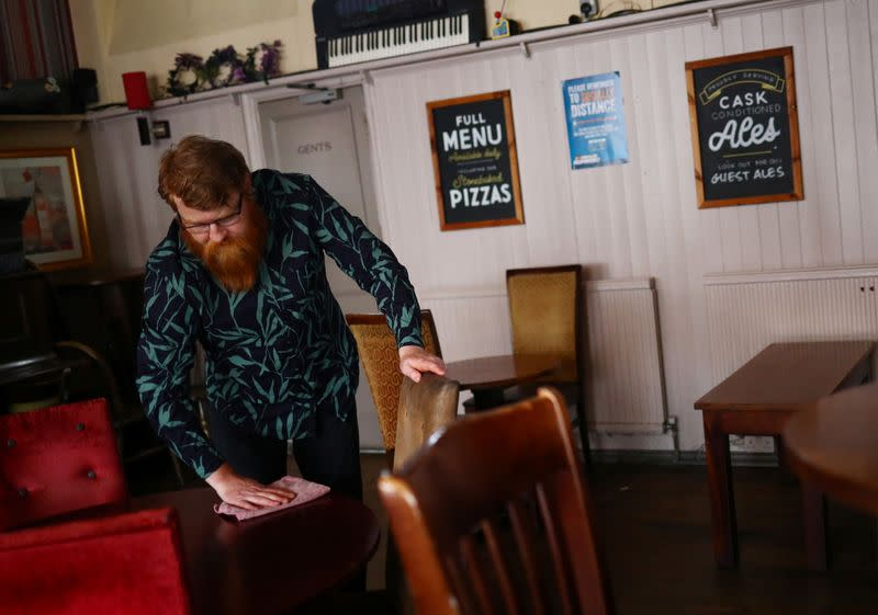 Landlord Are Kolltveit cleans a table in the Chandos Arms pub ahead of pubs reopening following the coronavirus disease (COVID-19) outbreak, in London