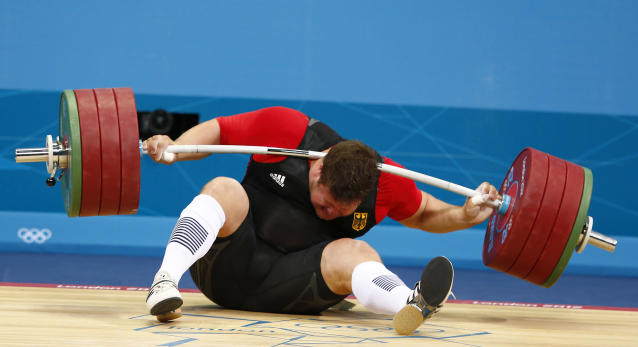 Germany's Matthias Steiner is injured while his weights fall during the men's 105kg Group A snatch weightlifting competition at the ExCel venue during the London 2012 Olympic Games August 7, 2012. REUTERS/Grigory Dukor (BRITAIN - Tags: OLYMPICS SPORT WEIGHTLIFTING TPX IMAGES OF THE DAY) FOR BEST QUALITY IMAGE: ALSO SEE GF2E88U0TO901.