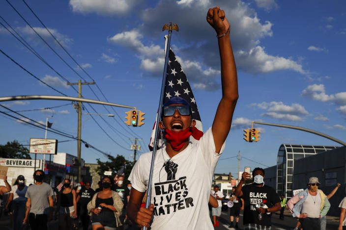 FILE - In this July 13, 2020, file photo, a protester carrying a U.S. flag leads a chant during a Black Lives Matter march through a residential neighborhood calling for racial justice, in Valley Stream, N.Y. (AP Photo/John Minchillo, File)