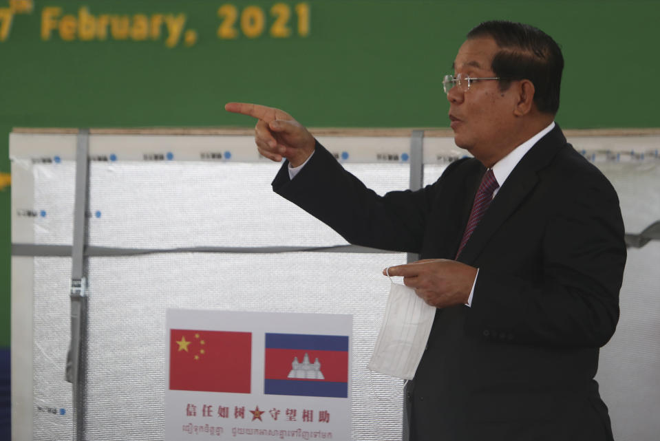 "Cambodian Prime Minister Hun Sen gestures during a handover ceremony at Phnom Penh International Airport, in Phnom Penh, Cambodia, Sunday, Feb. 7, 2021. Cambodia on Sunday received its first shipment of COVID-19 vaccine, a donation of 600,000 doses from China, the country's biggest ally. Beijing has been making such donations to several Southeast Asian and African nations in what has been dubbed ""vaccine diplomacy,"" aimed especially at poorer countries like Cambodia. (AP Photo/Heng Sinith)"