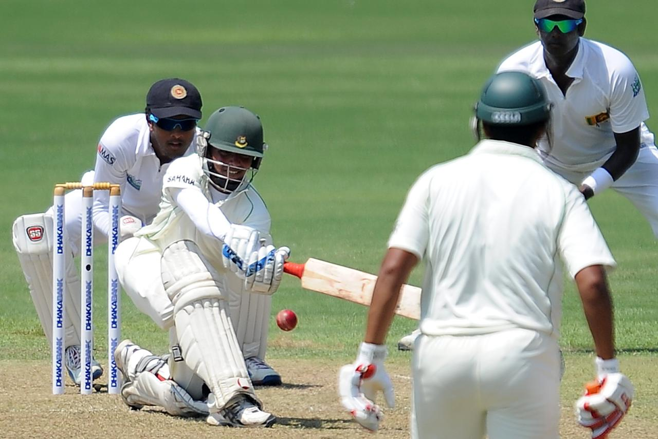 Bangladeshi cricketer Mominul Haque (2L) is watched by Sri Lankan wicketkeeper Dinesh Chandimal (L) as he plays a shot during the opening day of their second Test cricket match between Sri Lanka and Bangladesh at the R. Premadasa Cricket Stadium in Colombo on March 16, 2013.  AFP PHOTO/ LAKRUWAN WANNIARACHCHI