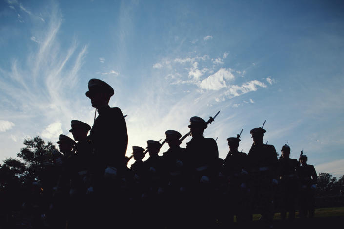 Low-angle view of silhouette cadets marching in platoon