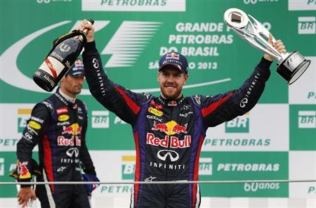 Red Bull Formula One driver Sebastian Vettel (R) of Germany celebrates his win on the podium in front of teammate Mark Webber of Australia after the Brazilian F1 Grand Prix at the Interlagos circuit in Sao Paulo November 24, 2013. REUTERS/Nacho Doce