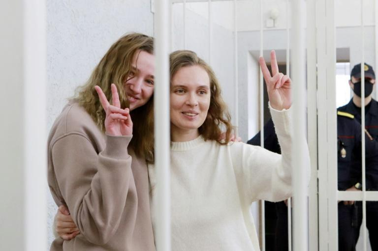 Daria Chultsova, left, and Katerina Bakhvalova flash a V for victory sign from a defendant's cage during their trial in Minsk on February 18, 2021