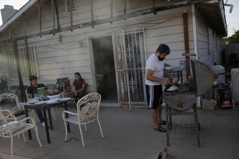 In this April 24, 2020, photo, Victor Chicas, right, cooks dinner behind his home as his niece Damaris Arevalos, center, and nephew Mario Arevalos wait in Las Vegas. Chicas, a restaurant server in the Mandalay Bay casino-hotel, was facing foreclosure on his home before the virus shut down the city and the 54-year-old was laid off. (AP Photo/John Locher)