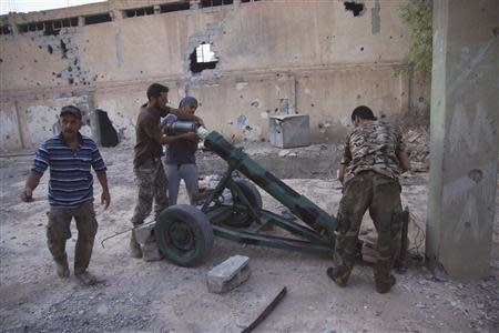 Free Syrian Army fighters prepare to launch rocket against forces loyal Syria's President al-Assad in Deir al-Zor