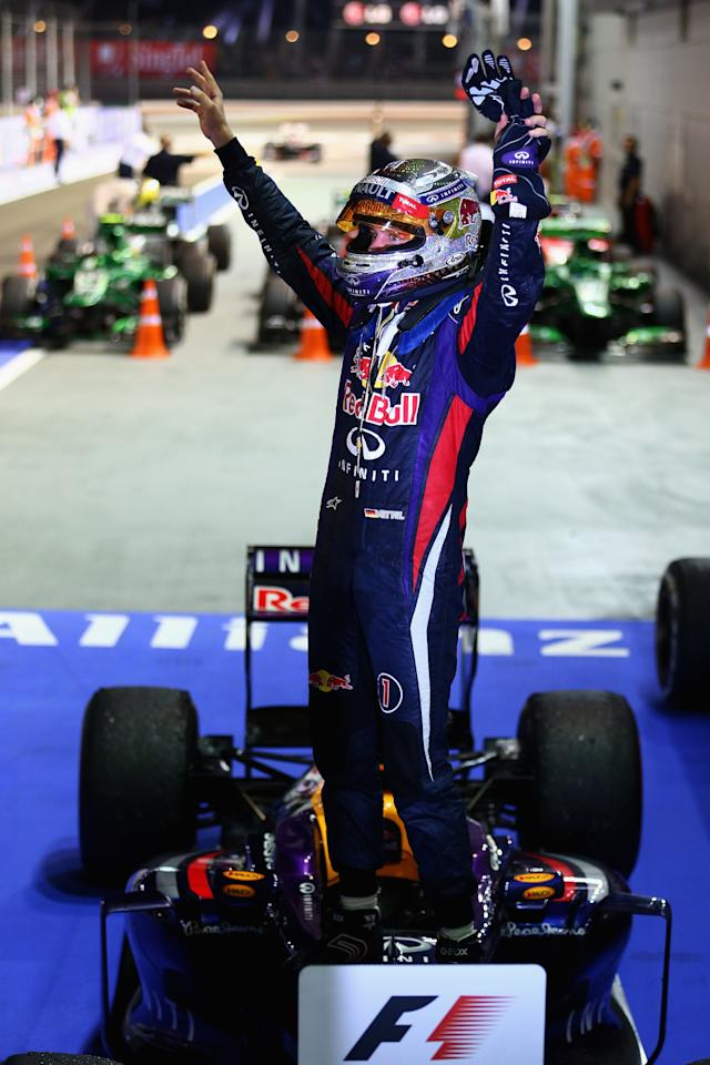 SINGAPORE - SEPTEMBER 22: Sebastian Vettel of Germany and Infiniti Red Bull racing celebrates following his victory during the Singapore Formula One Grand Prix at Marina Bay Street Circuit on September 22, 2013 in Singapore, Singapore. (Photo by Paul Gilham/Getty Images)